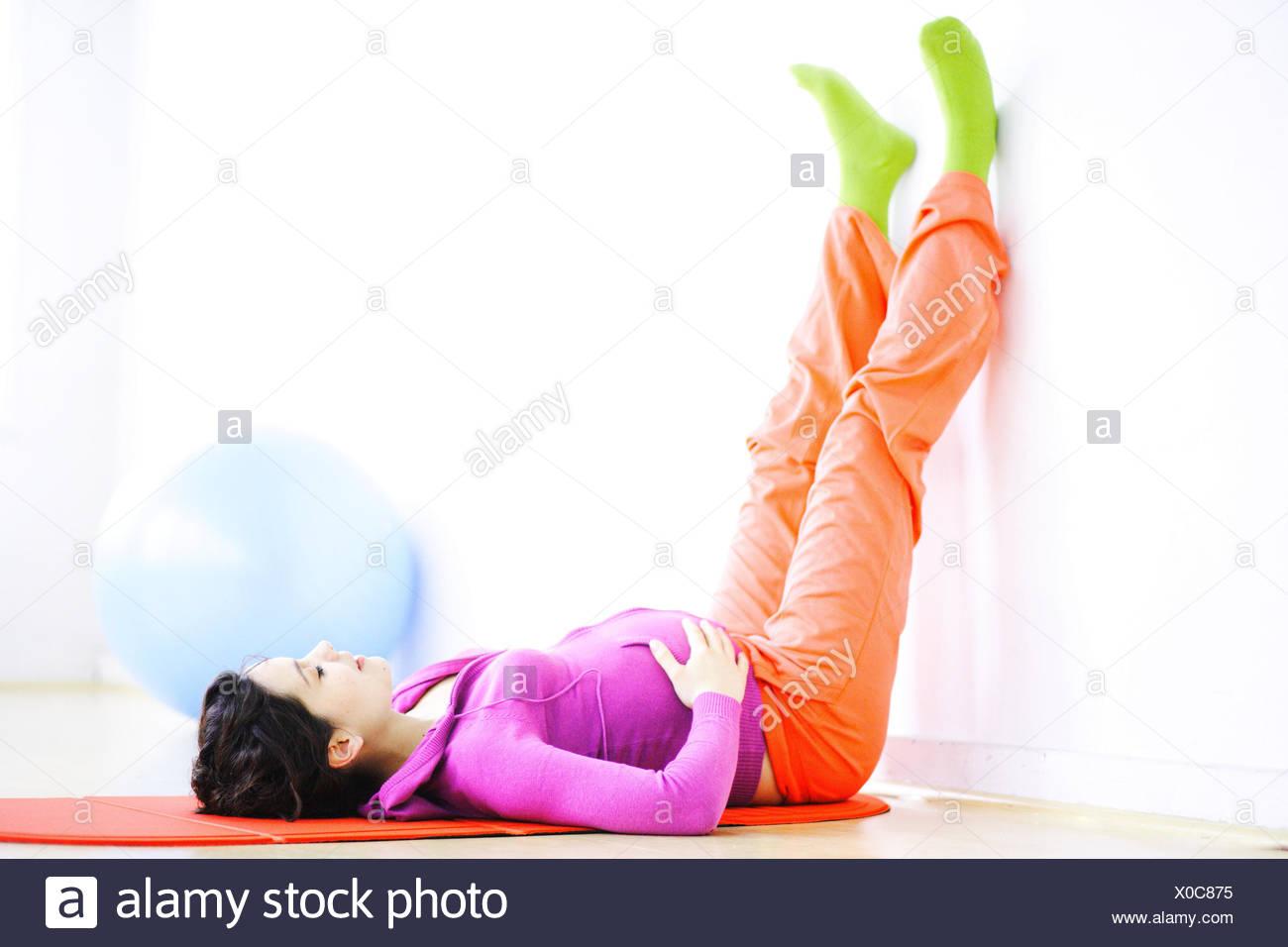Pregnant woman performing prenatal exercises. - Stock Image