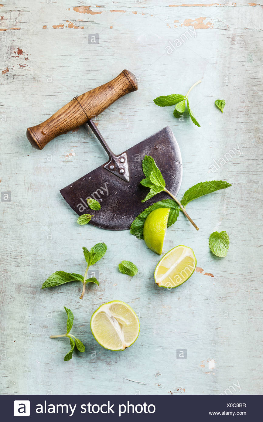 Ingredients for making mojitos mint leaves and lime on blue background - Stock Image