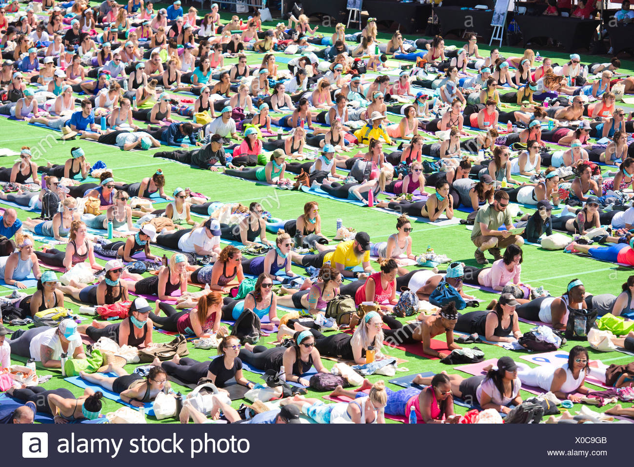 People performing sphinx pose during outdoor yoga festival on Santa Monica Pier in Santa Monica, California, USA - Stock Image