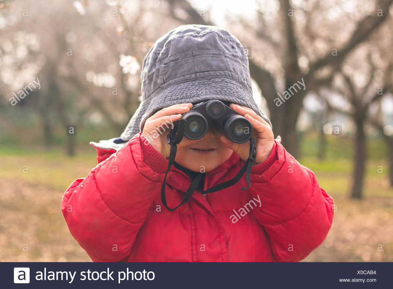 Boy (2-3) looking trough binoculars - Stock Image