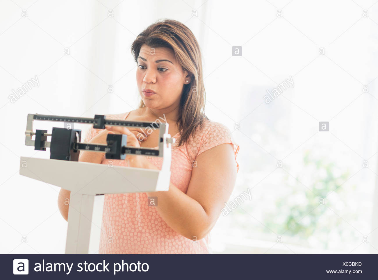 Woman standing on scale - Stock Image