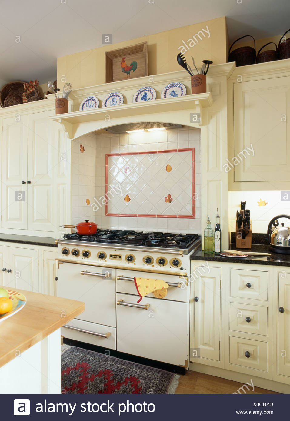 White and red wall tiles above white range oven in ...