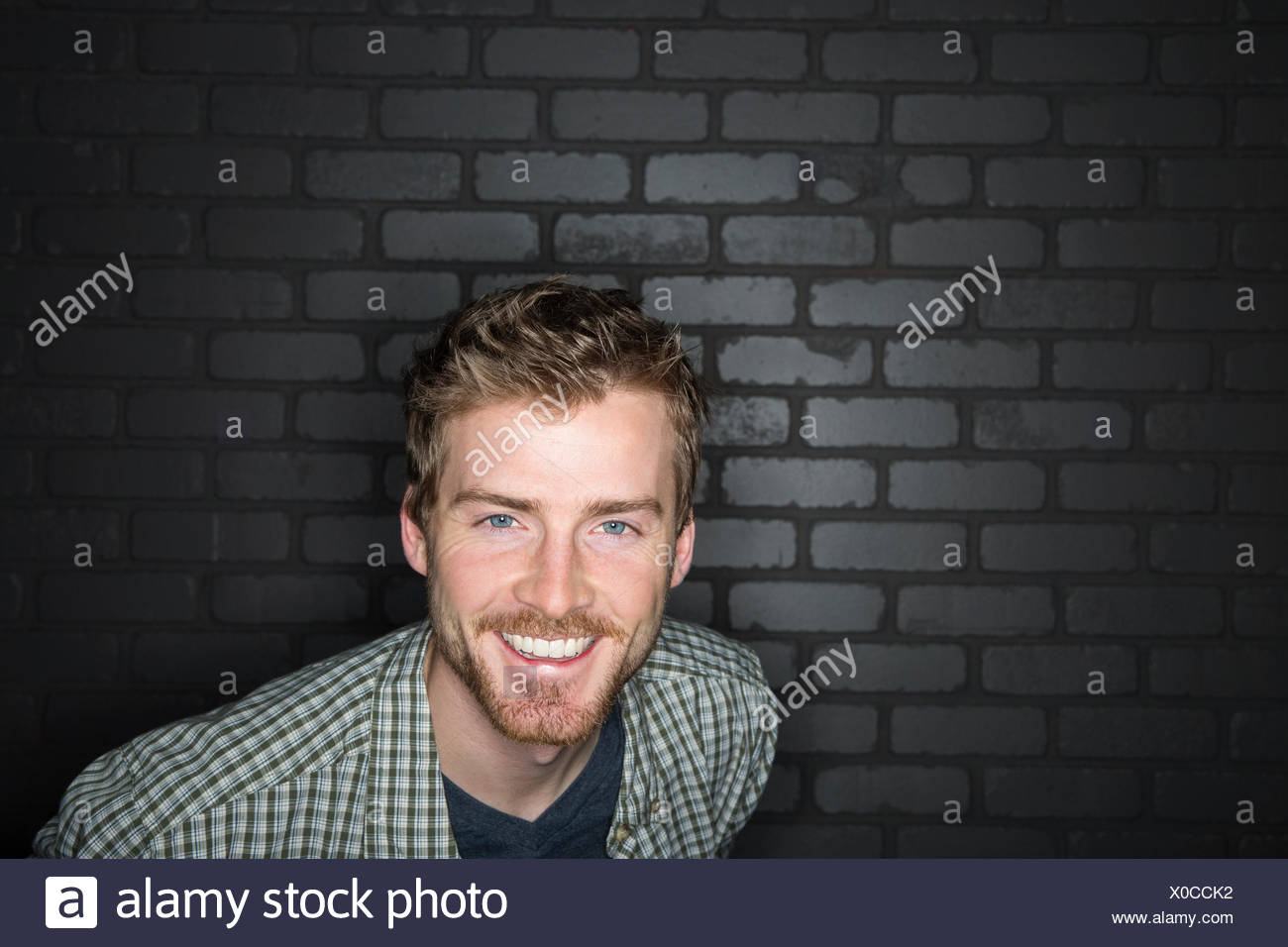 Portrait of enthusiastic man in plaid shirt - Stock Image