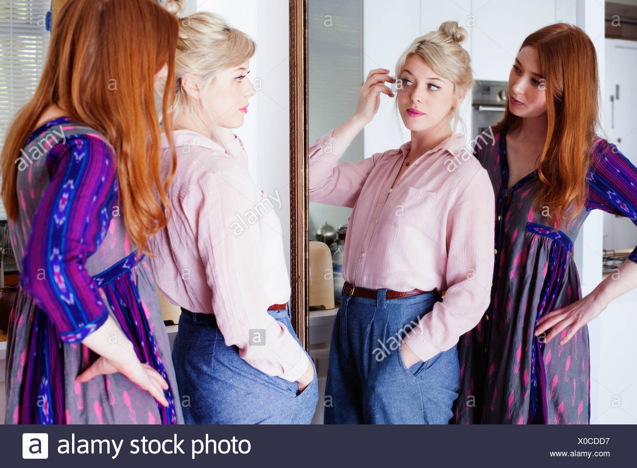 Young women looking in mirror - Stock Image