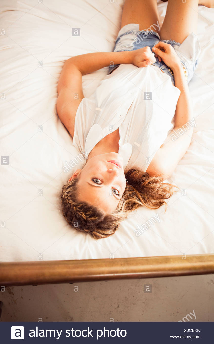 Young woman lying on bed looking at camera - Stock Image
