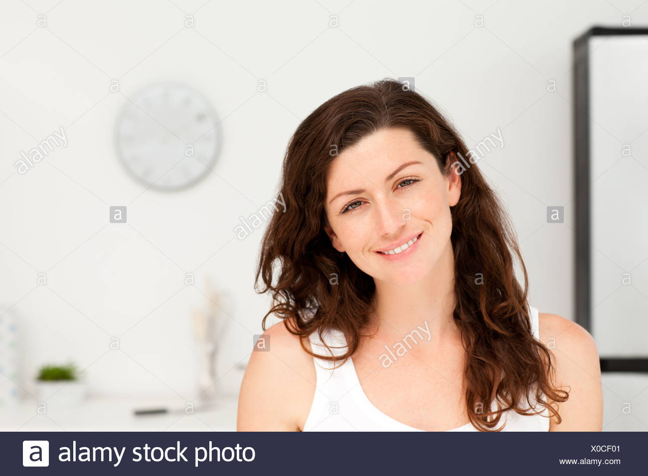 Portrait of a radiant woman in pyjama in her kitchen - Stock Image