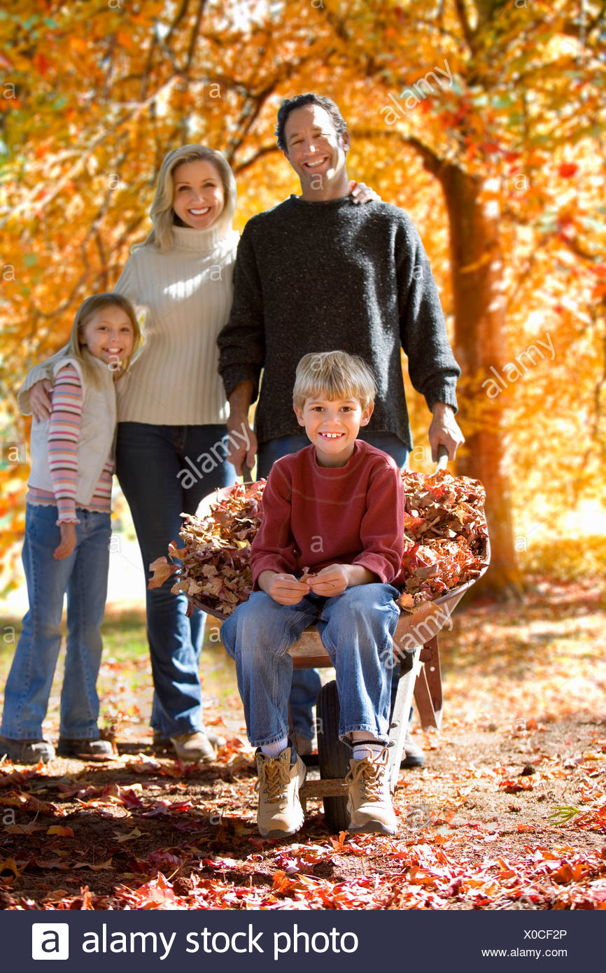 Family doing yard work in autumn - Stock Image