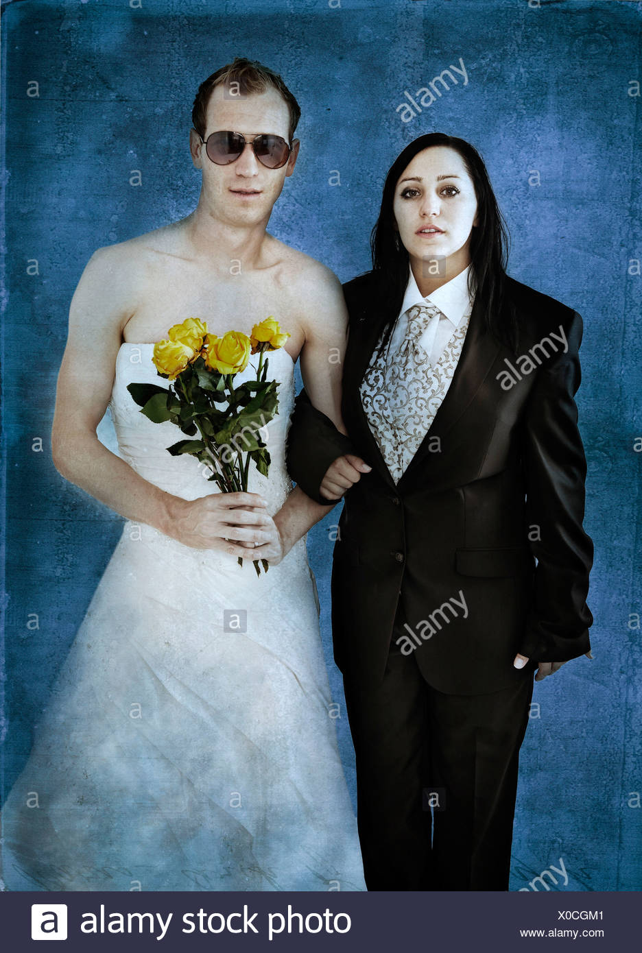 Bride wearing a suit and a groom wearing a wedding dress with ...