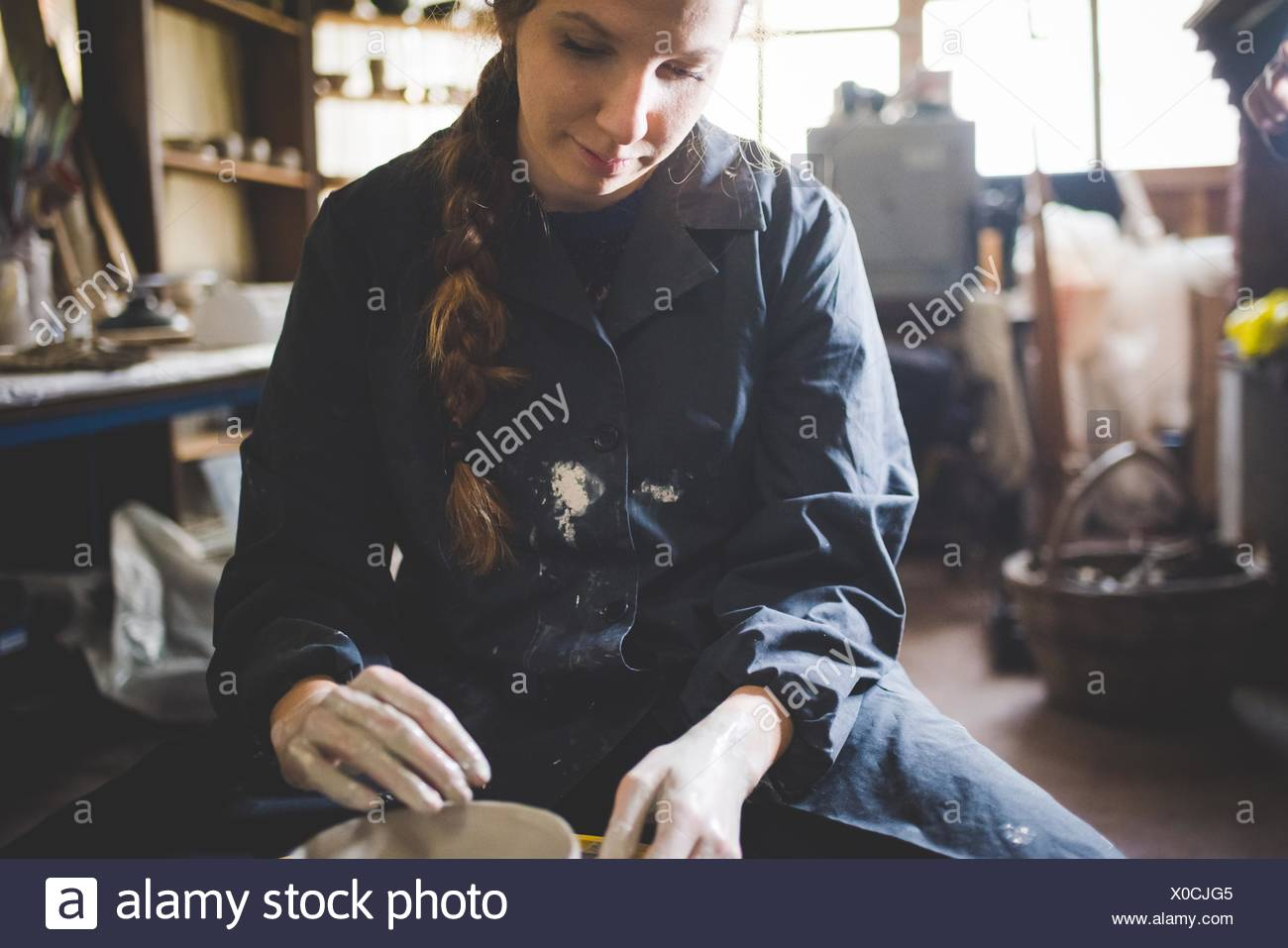 Front view of young woman sitting at pottery wheel looking down making clay pot - Stock Image