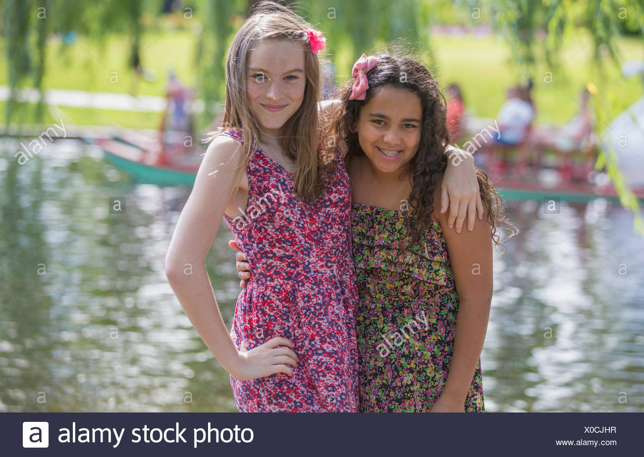 Portrait of two Hispanic teen sisters posing together in a park - Stock Image