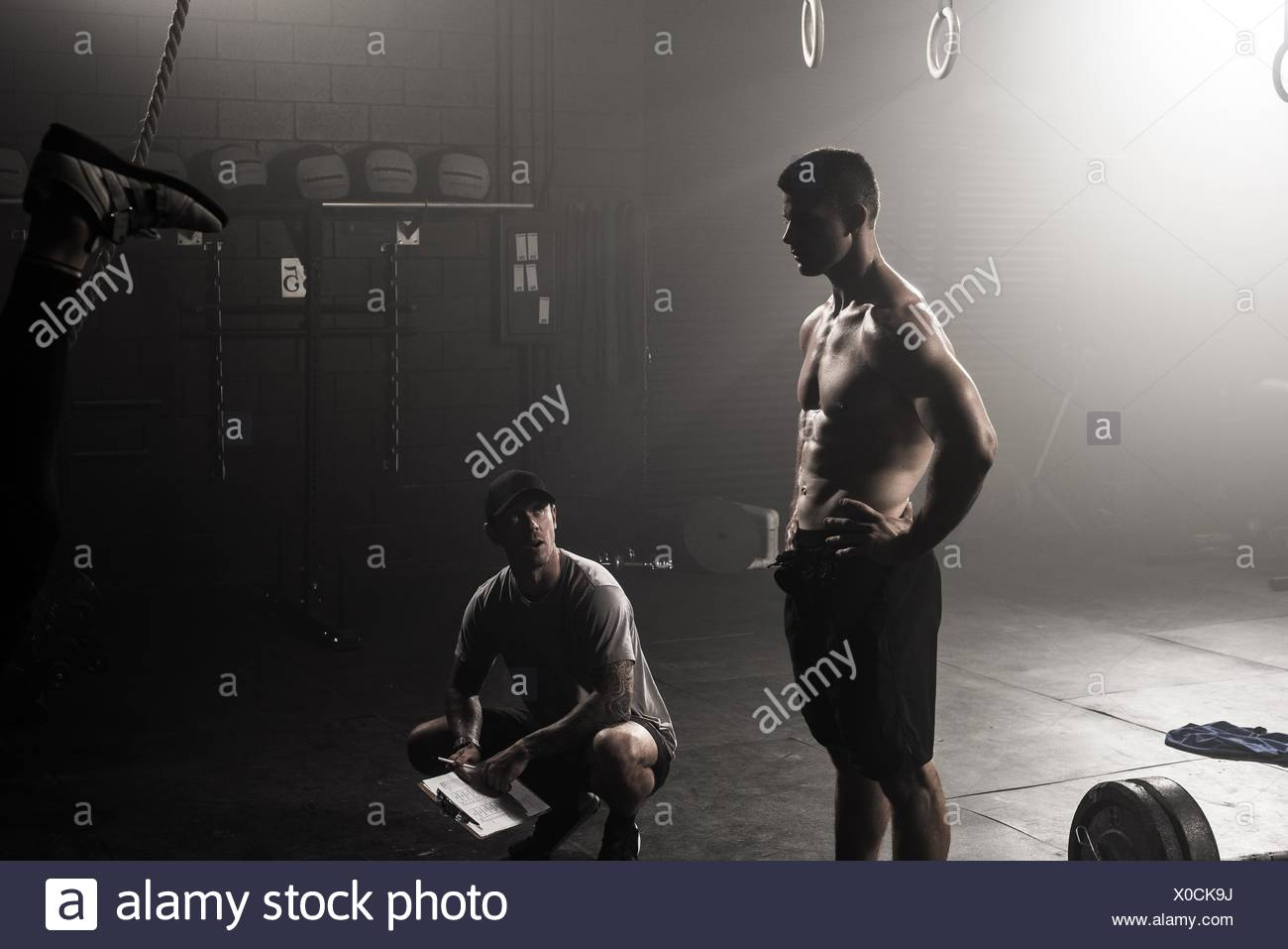 Young man and trainer in gym - Stock Image