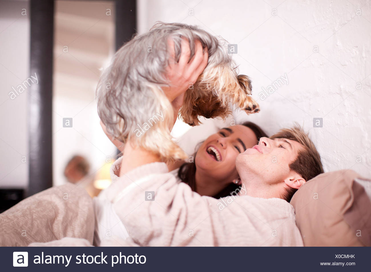 Young couple in bed with pet dog - Stock Image