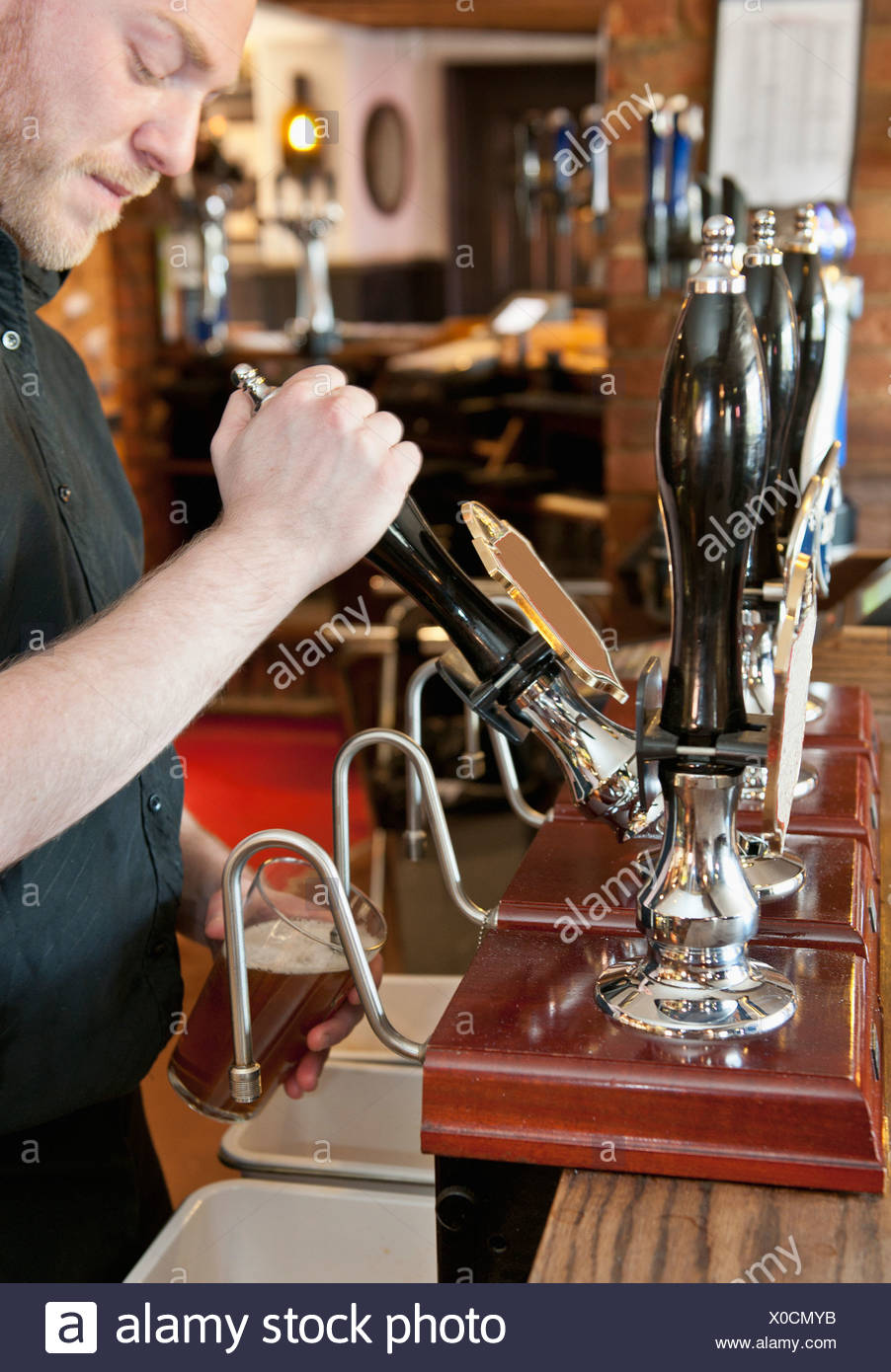 Bartender pouring beer at bar - Stock Image