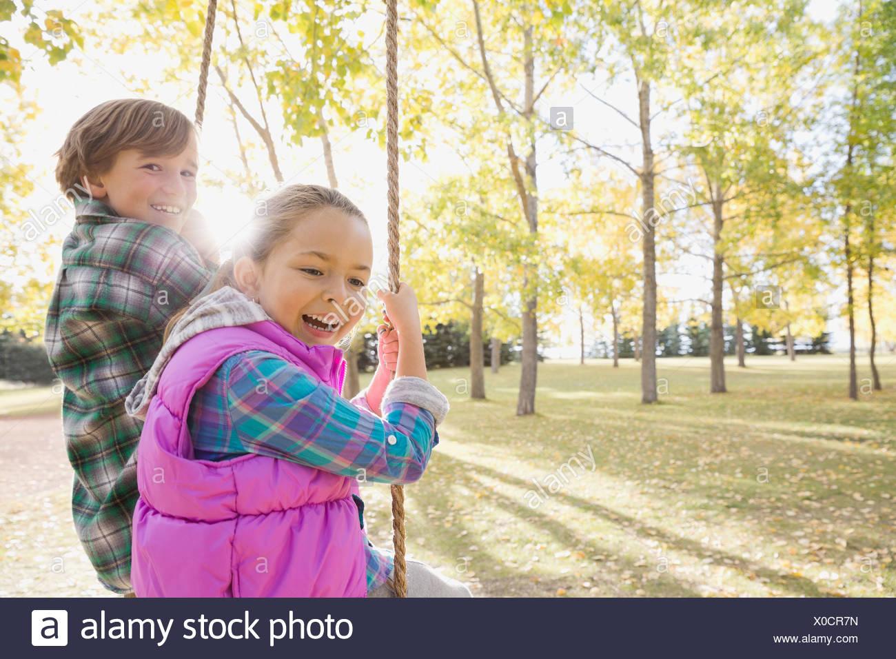 Siblings swinging at park Stock Photo