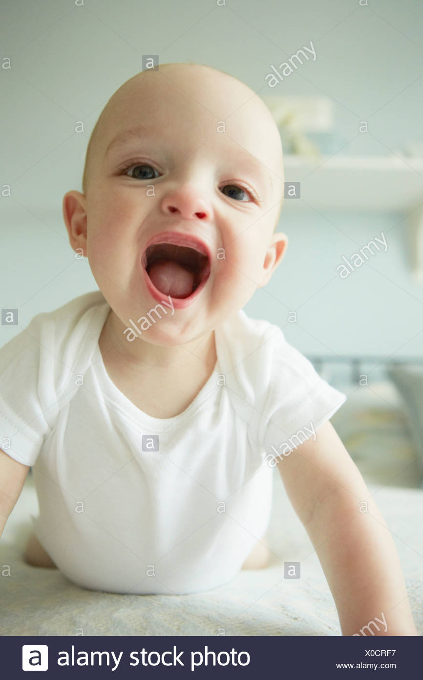 Baby boy crawling on bed - Stock Image