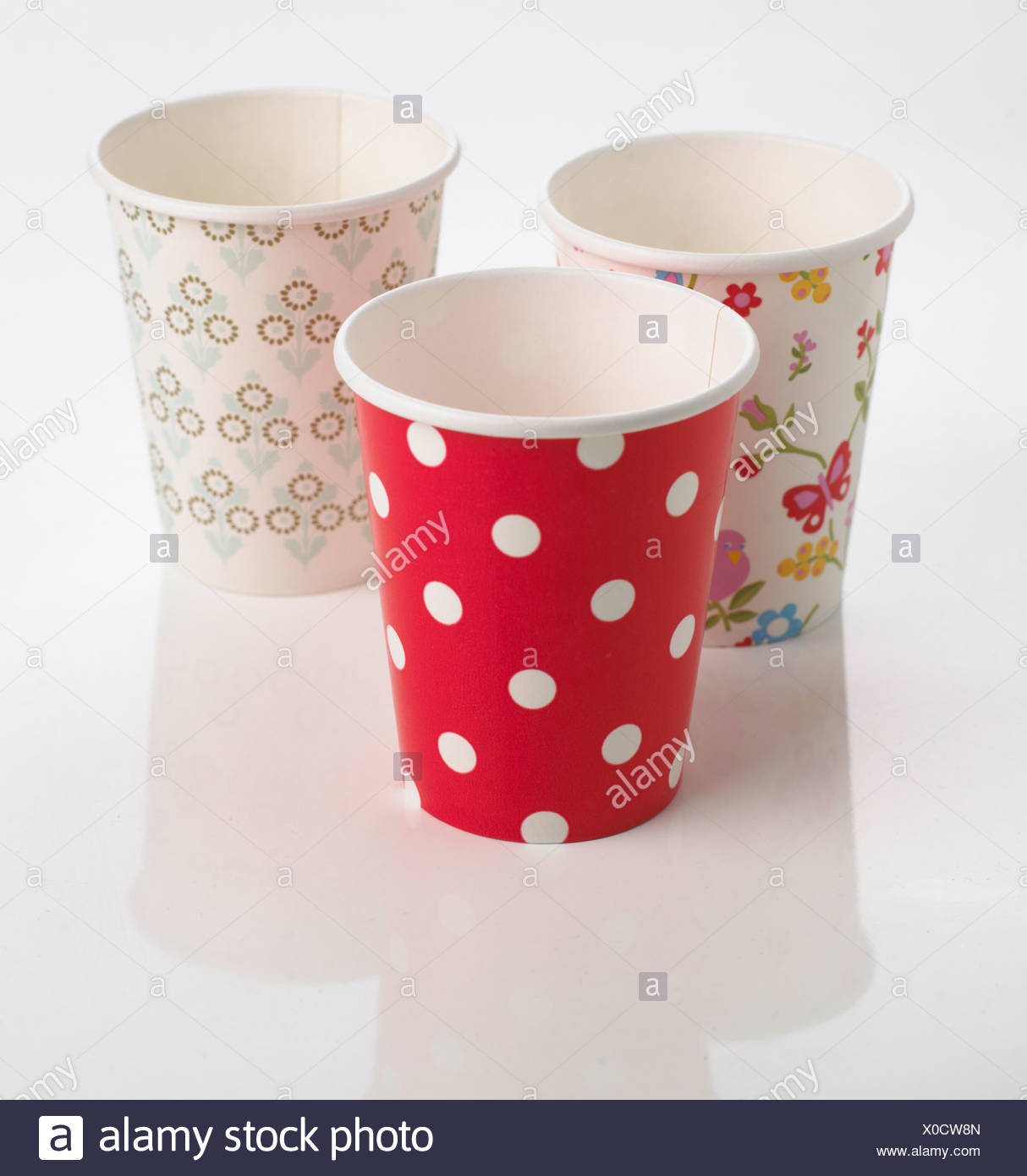 Three brightly coloured disposable paper cups - Stock Image