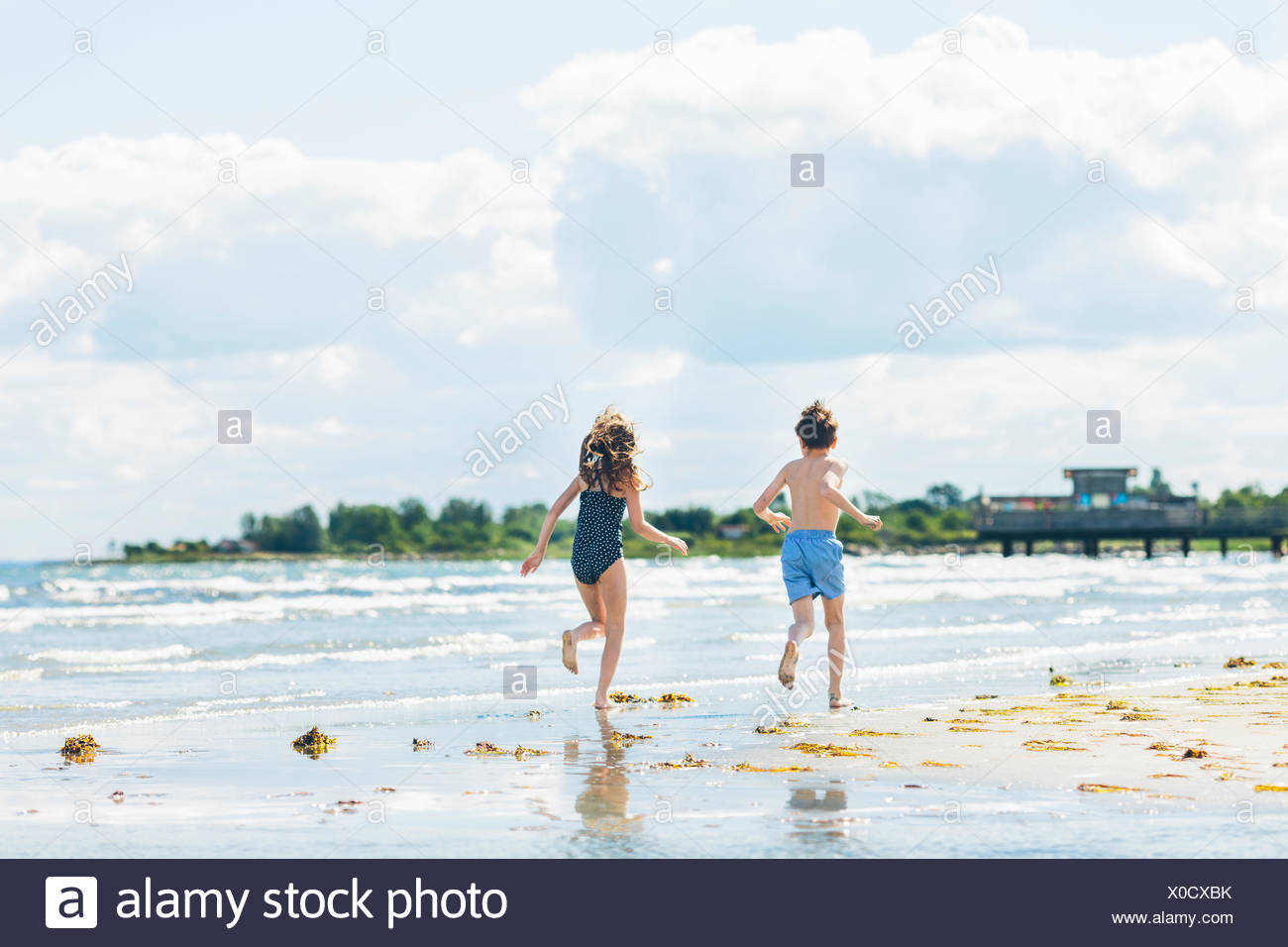 Girl (10-11) and boy (8-9) running on beach - Stock Image