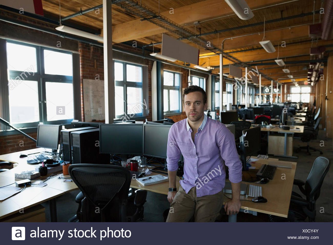 Portrait serious businessman in open office - Stock Image