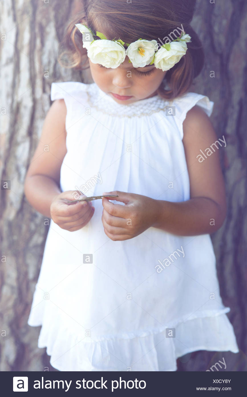 Portrait of a girl standing by tree wearing flower headdress Stock Photo