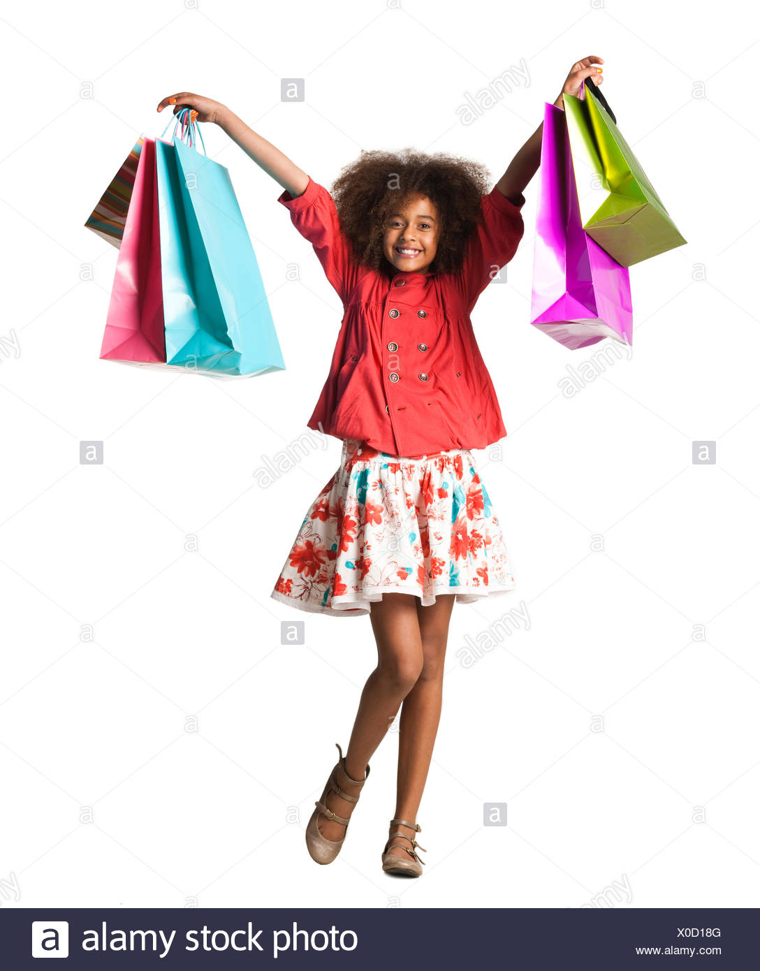 Teenage girl (12-13) holding aloft multi colored shopping bags,studio shot - Stock Image