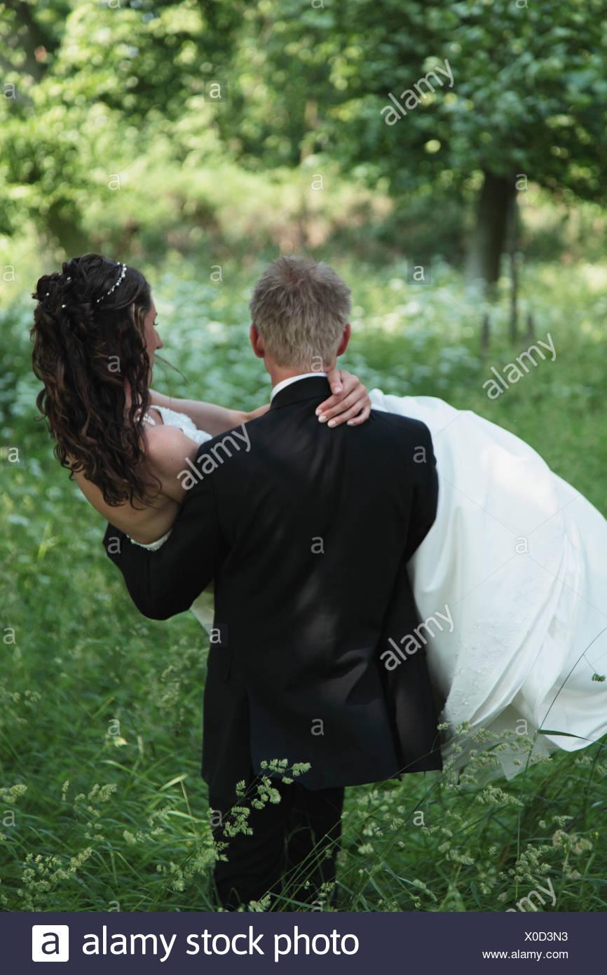 Man carries woman through grass - Stock Image