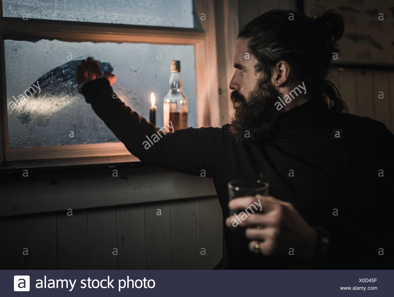 A man sitting alone in a room with a bottle of whisky and a glass, wiping condensation off window - Stock Image