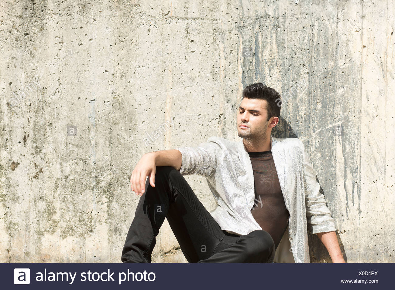 Man leaning against wall outdoors - Stock Image