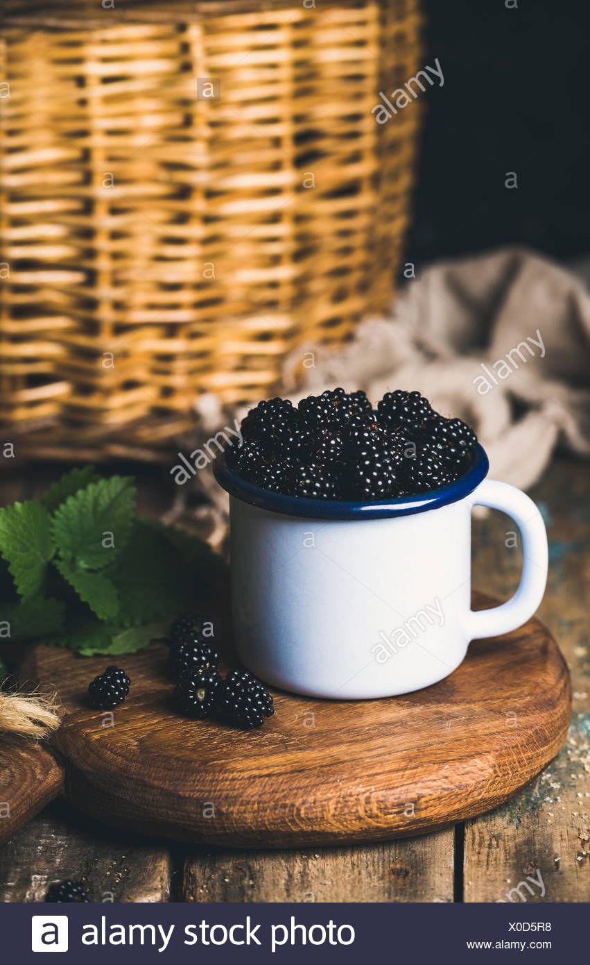 Fresh Blackberries in white cup on round serving wooden board over rustic background, selective focus, vertical composition - Stock Image