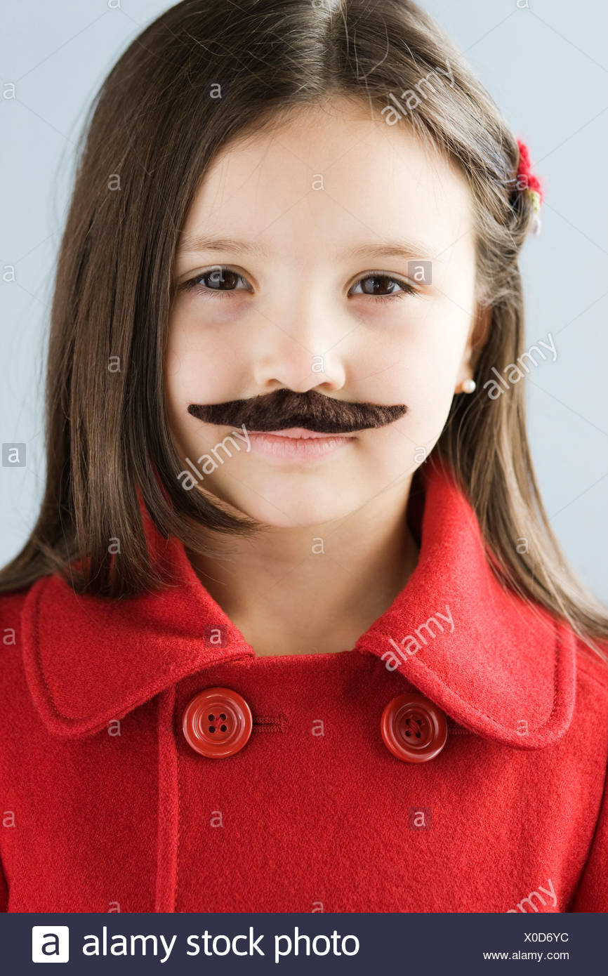 Studio portrait of girl (6-7) wearing fake moustache - Stock Image