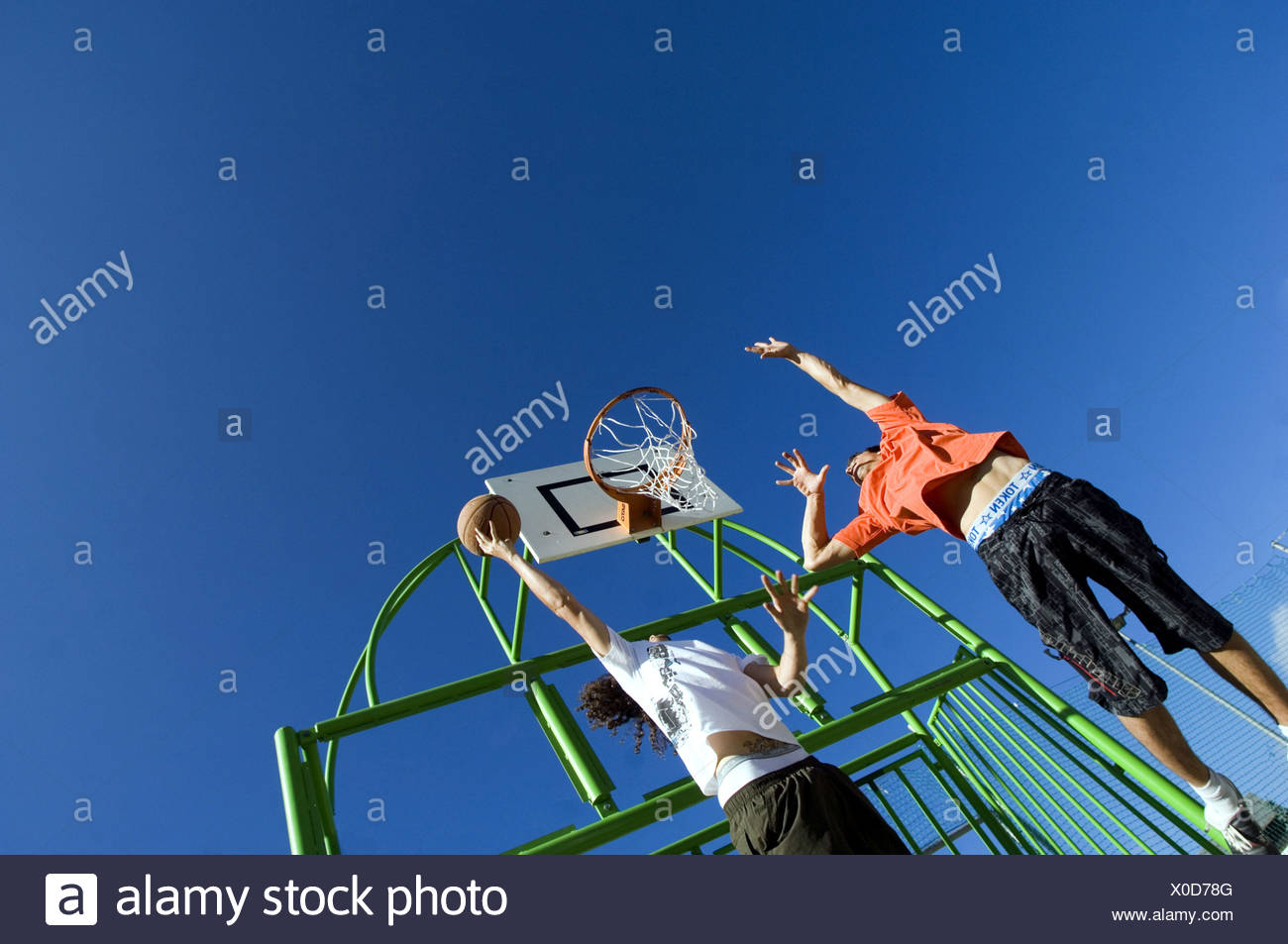 adolescents playing basket ball - Stock Image