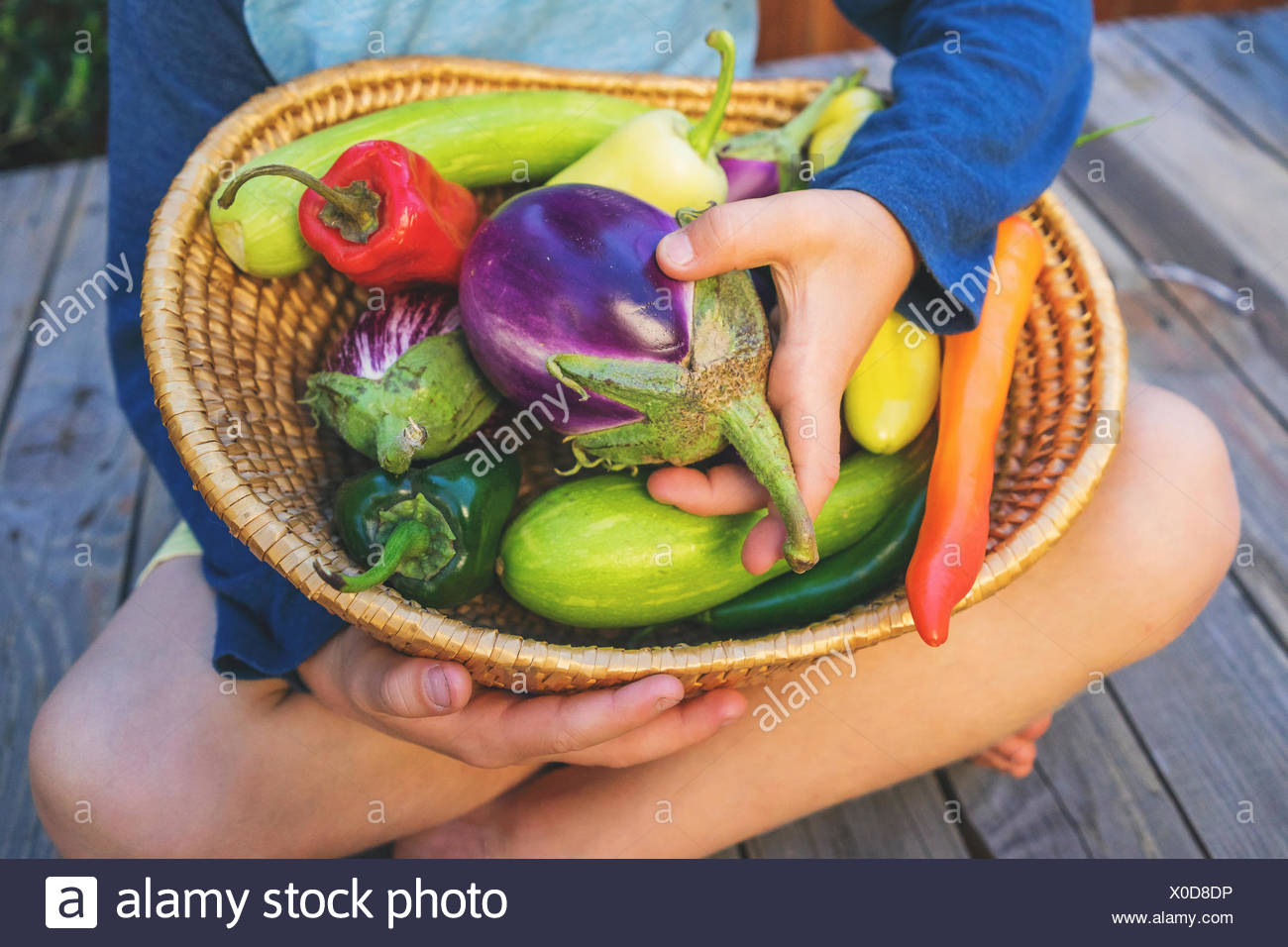 Boy sitting cross legged with a basket of vegetables - Stock Image