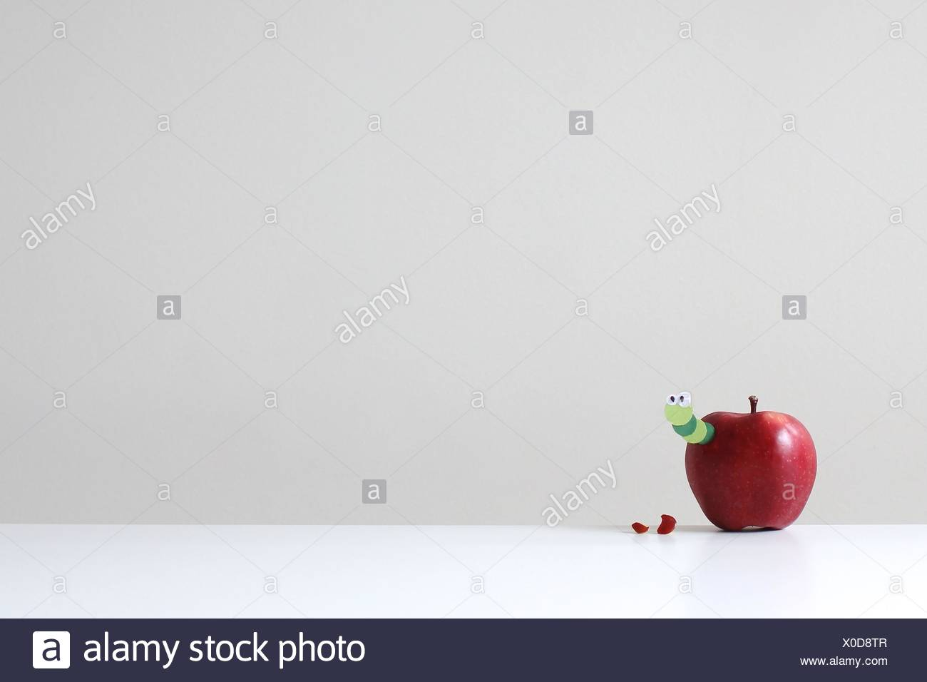 A red apple with a green paper worm poking out - Stock Image