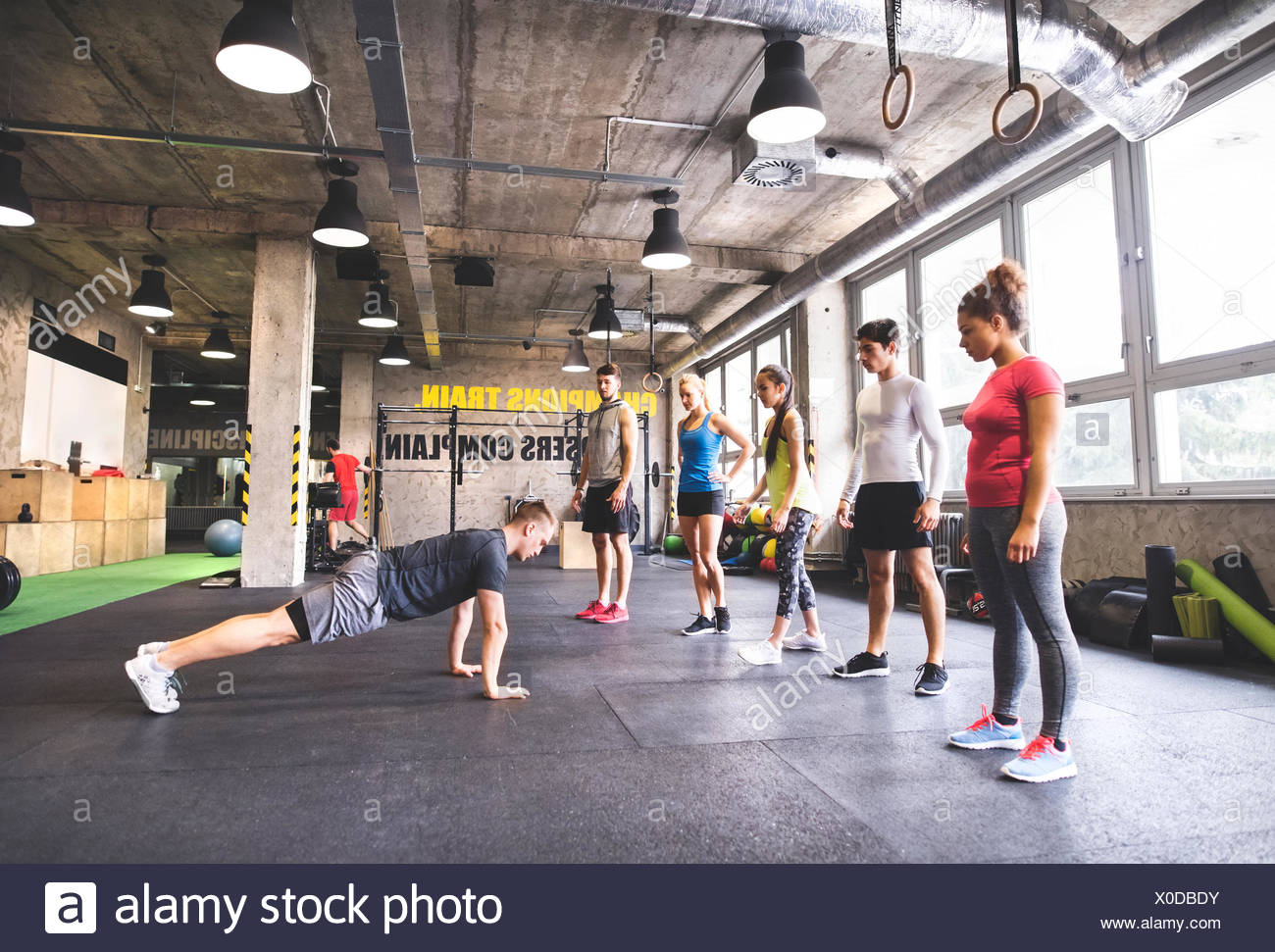 Group of young people watching young man doing push-ups in gym - Stock Image