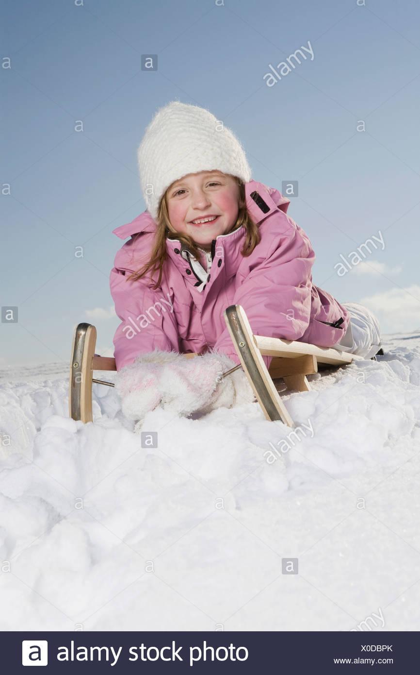 Germany, Bavaria, Munich, Girl (6-7) lying on sledge, smiling, portrait - Stock Image