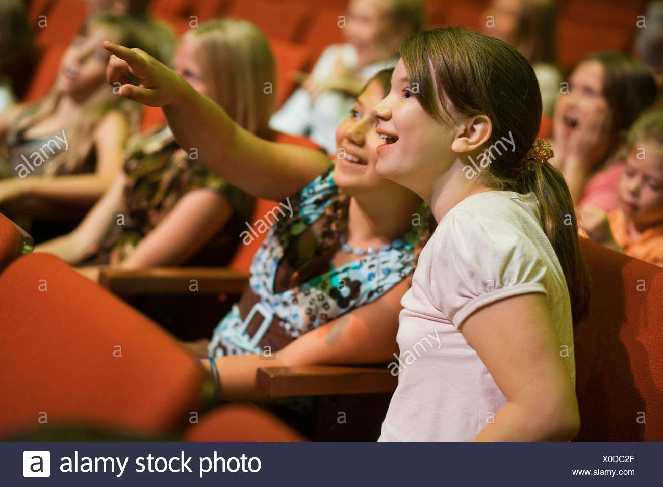 Girls pointing in theatre seats - Stock Image