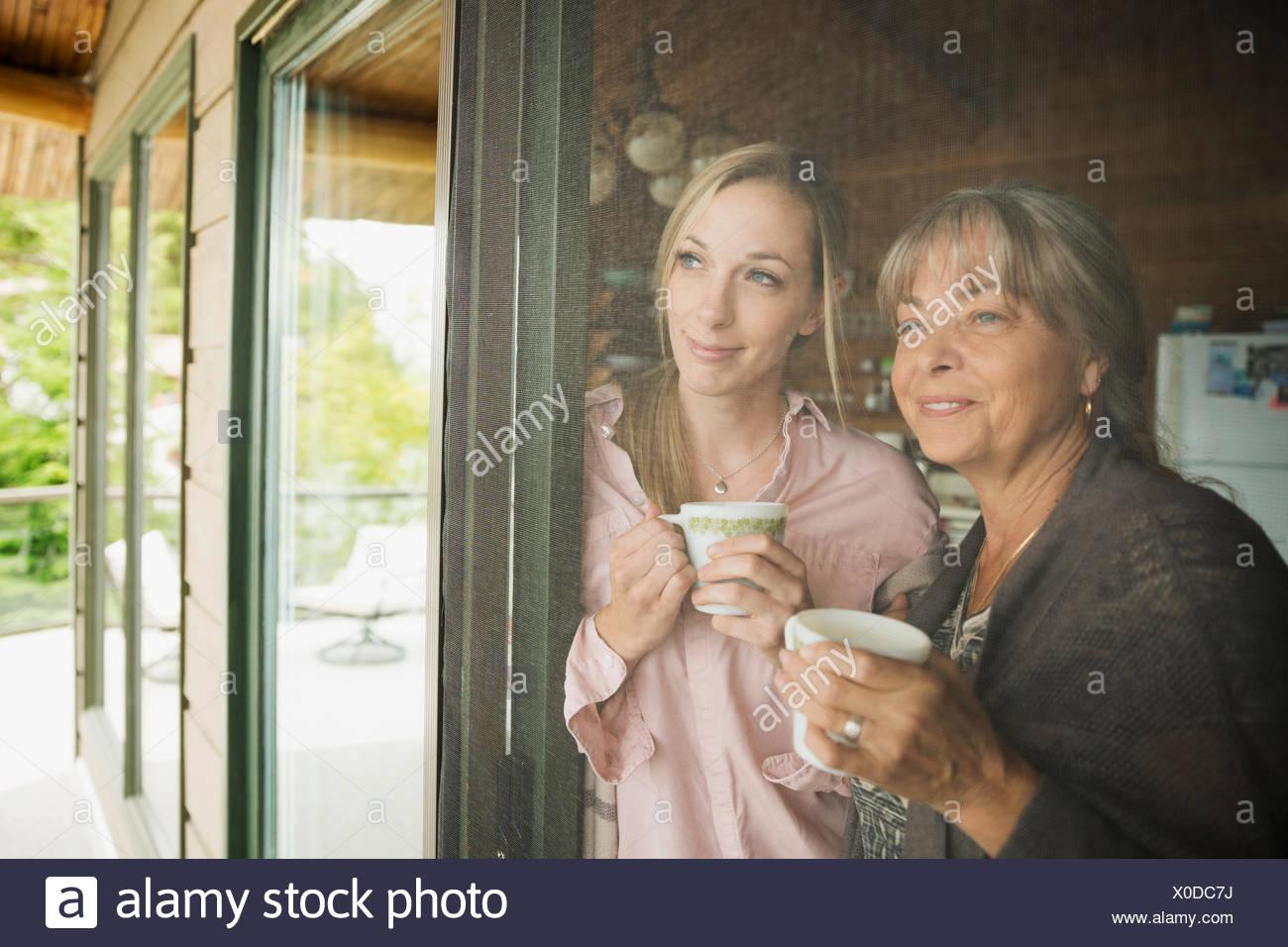 Mother and daughter drinking coffee cabin screen door - Stock Image