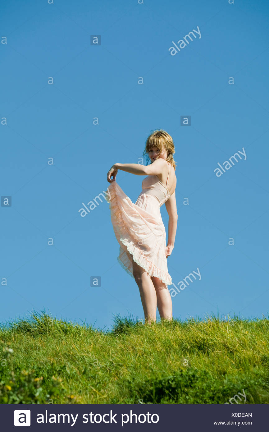USA, San Francisco, California, young woman standing on grassy hill - Stock Image