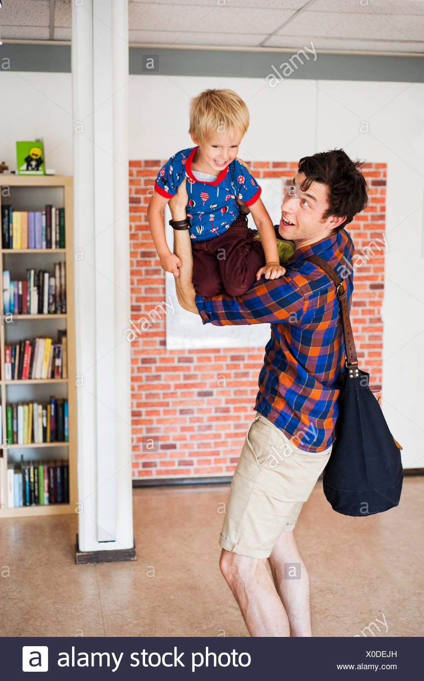Playful father lifting son at primary school - Stock Image