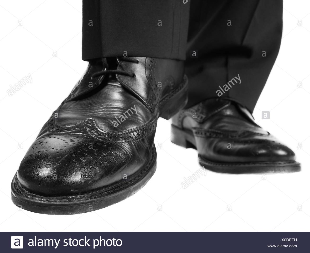 Black suit, black leather shoes approaching - Stock Image