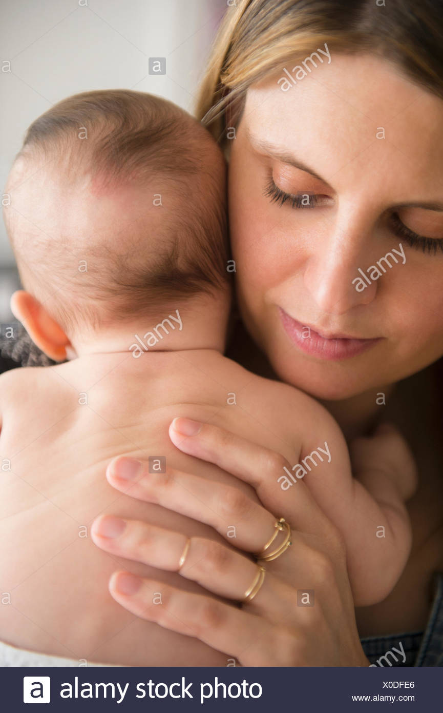 Mother holding baby girl (2-5 months) in her arms - Stock Image