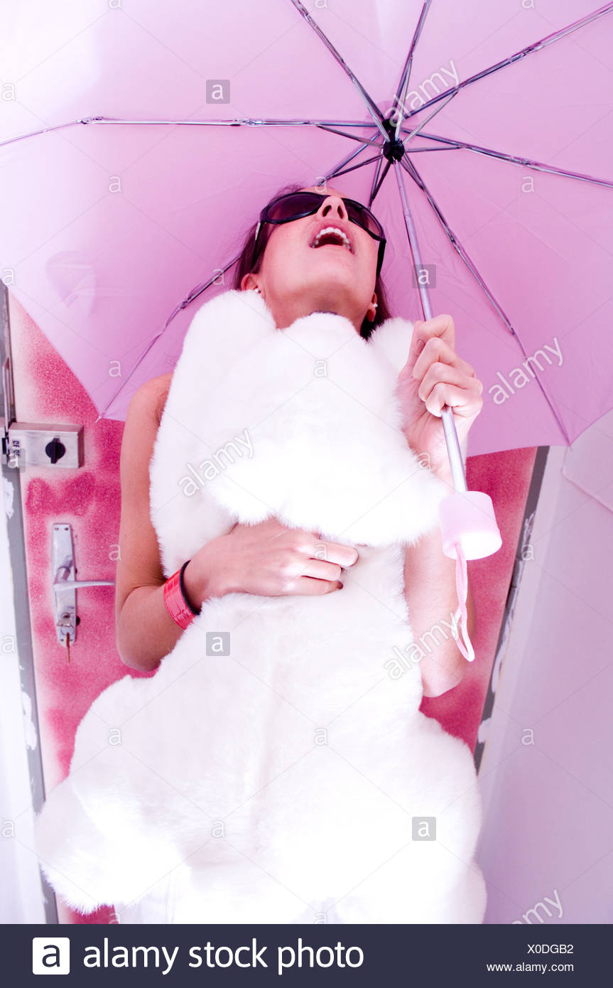 Low angle view of young woman holding teddy bear under umbrella - Stock Image