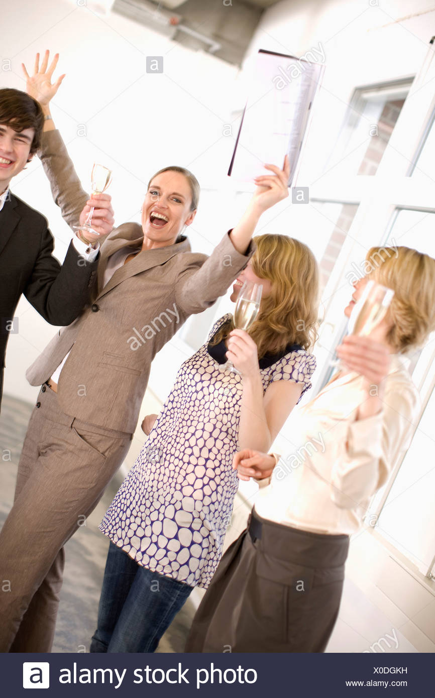 people drinking champagne in an office - Stock Image