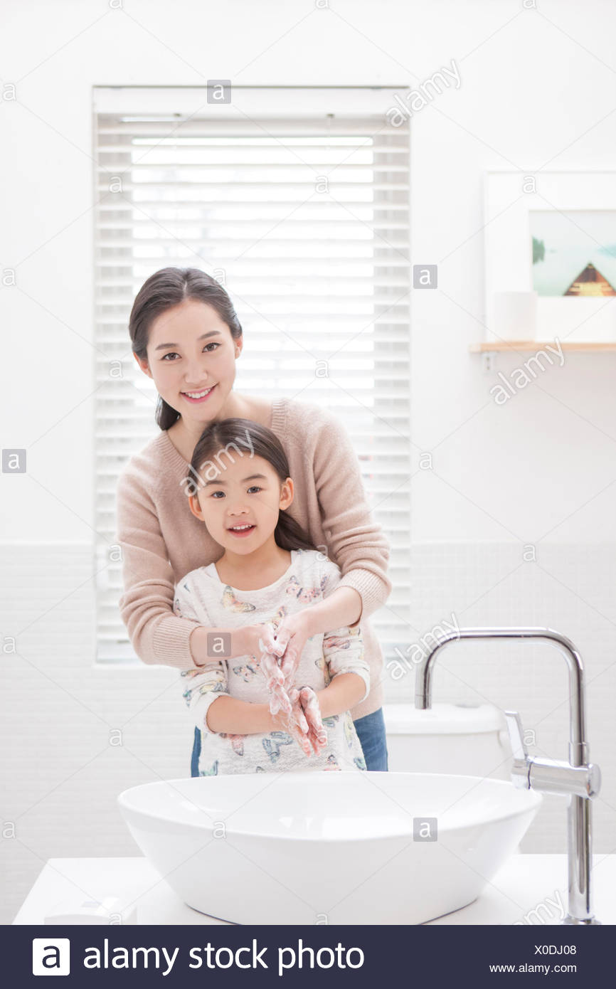 Smiling mother and daughter washing hands together in bathroom - Stock Image