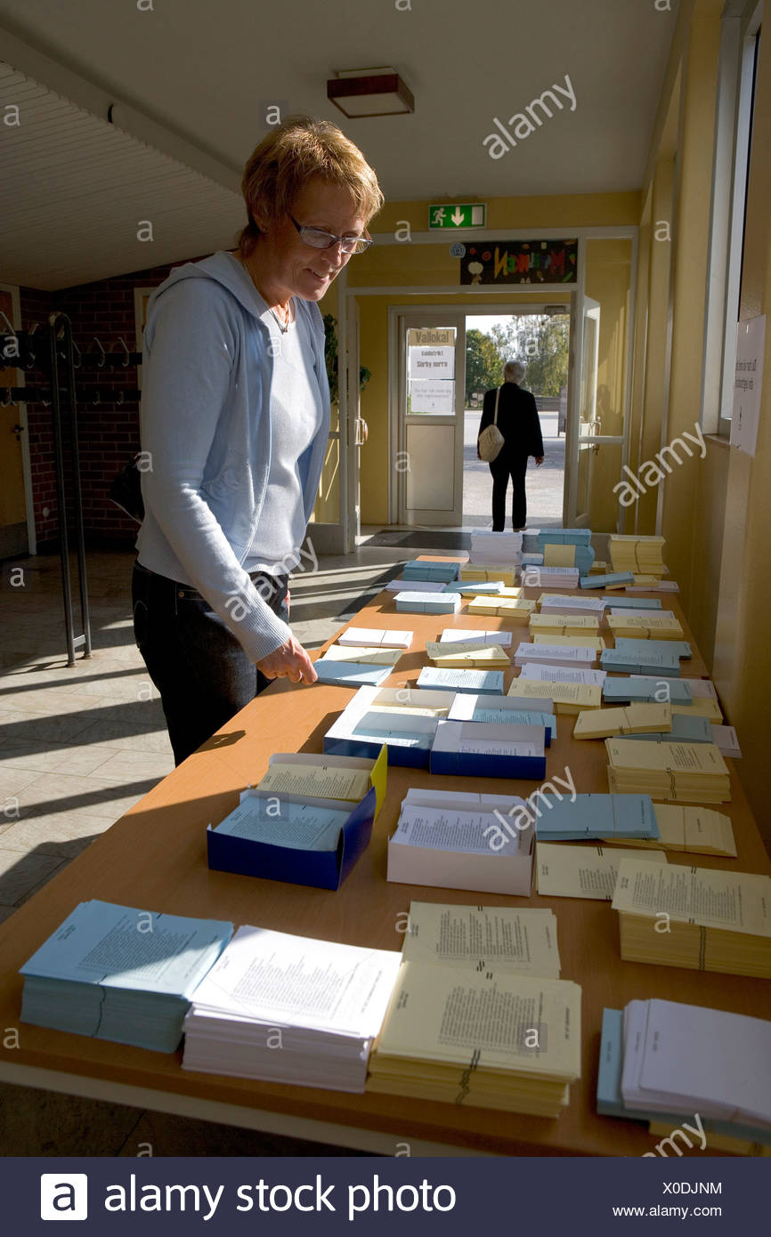 Side view of a middle-aged woman with ballots in the polling station - Stock Image