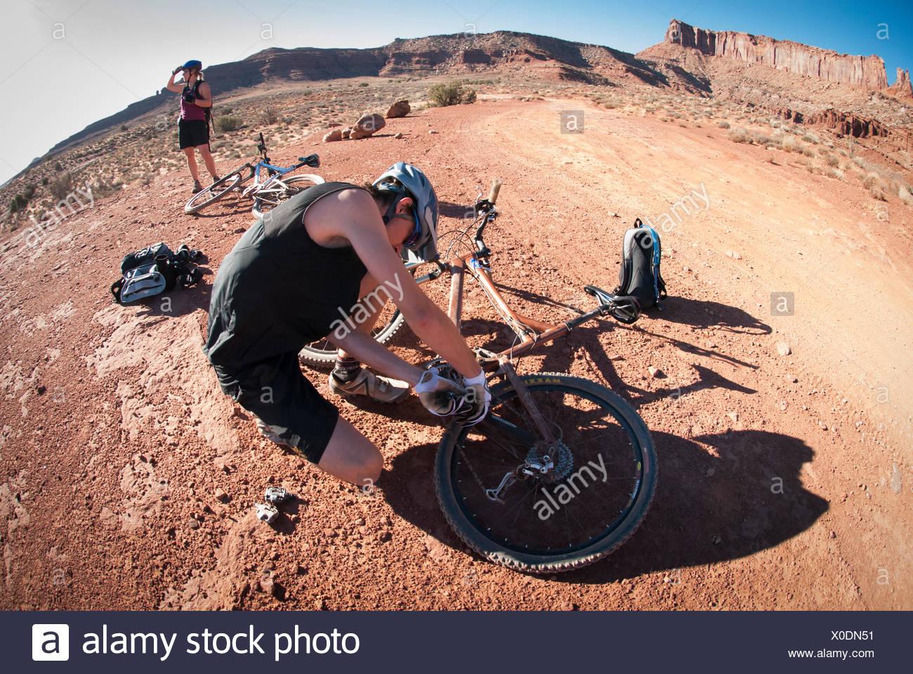 Riders tune up their mountain bikes while touring the White Rim Trail near Moab, Utah. - Stock Image