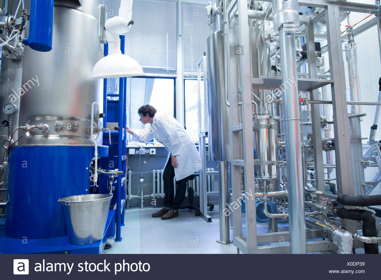 Woman with lab coat in technical room with a fermenter - Stock Image