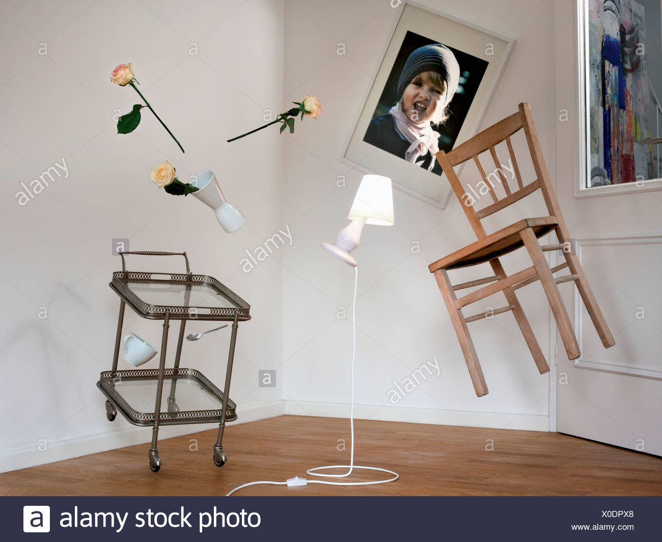 Chair, lamp and table floating in room - Stock Image