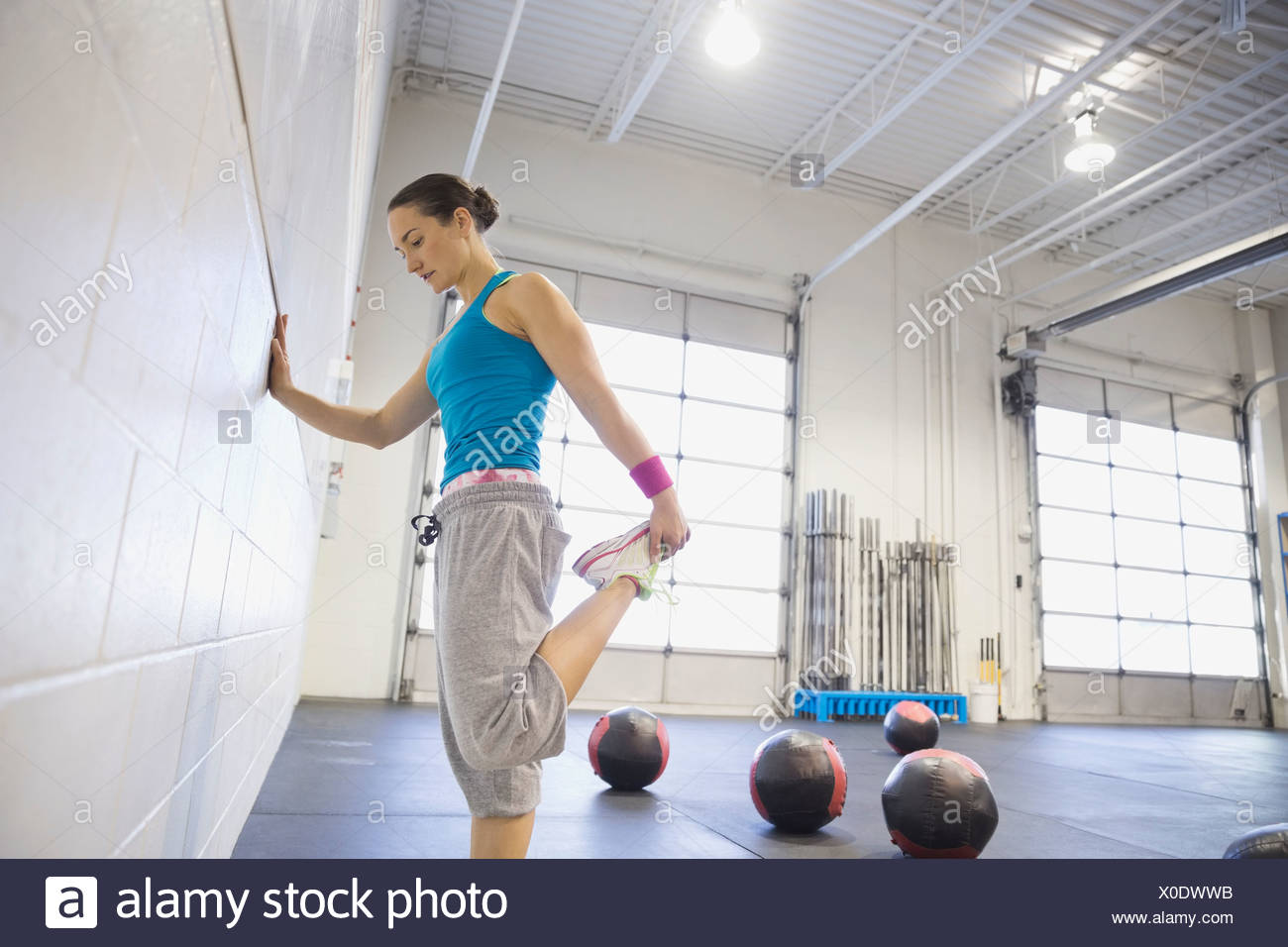 Woman stretching legs in gym - Stock Image