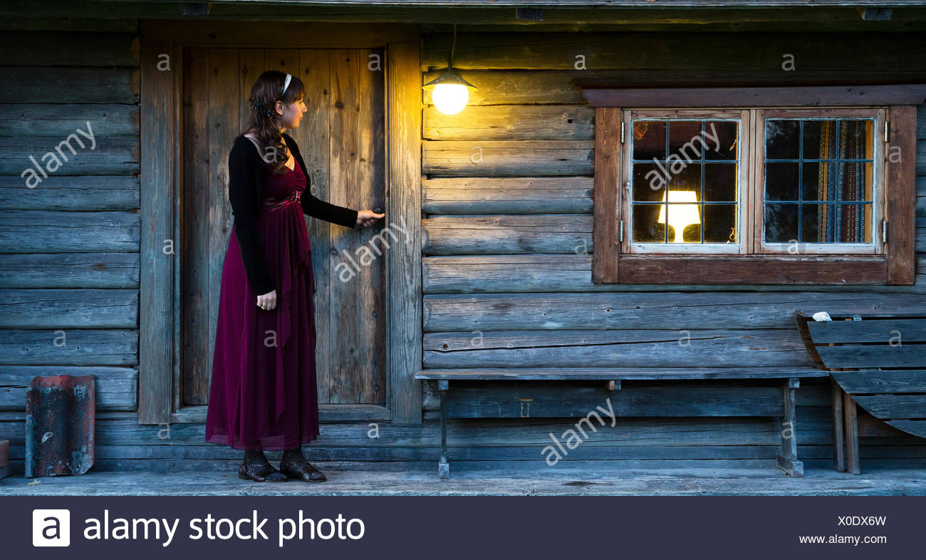 Woman in front of wooden house - Stock Image
