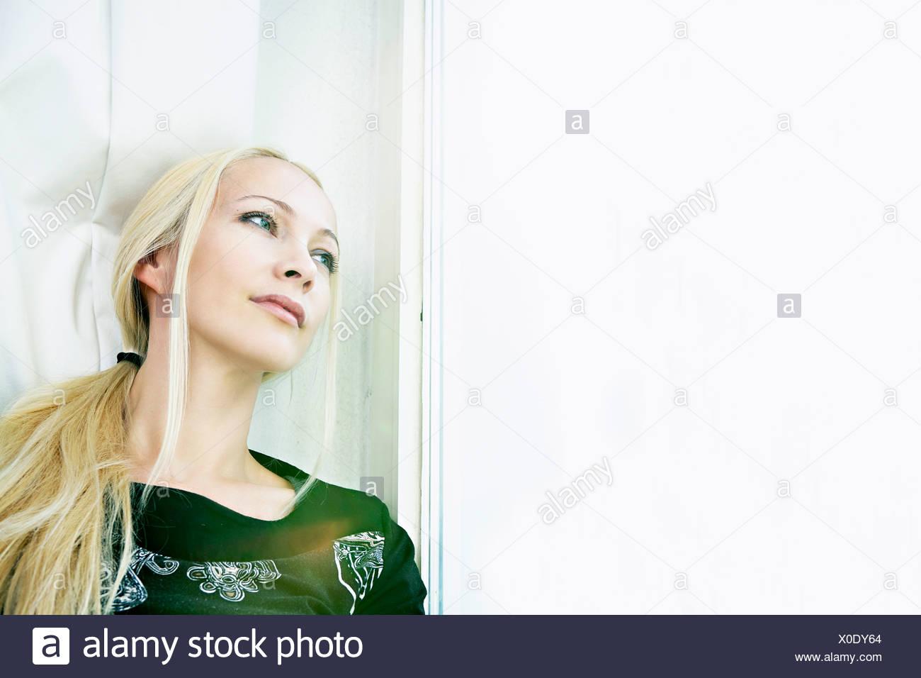 Blond woman day dreaming, Munich, Bavaria, Germany - Stock Image